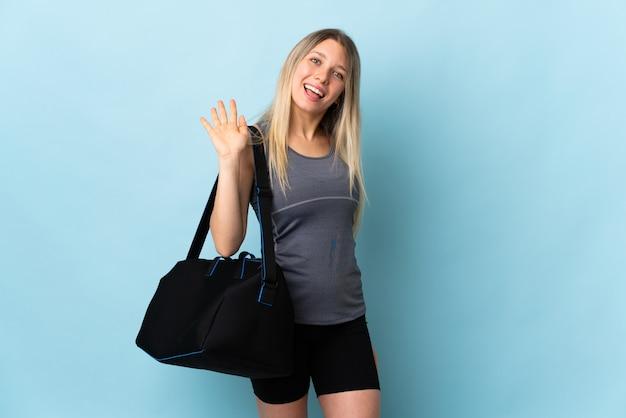 Młoda kobieta sport z torbą sportową na białym tle na niebieskiej ścianie, salutując ręką z happy wypowiedzi