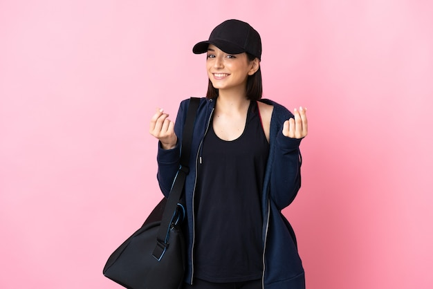 Młoda kobieta sport z torbą sportową na białym tle na różowo zarabianie pieniędzy gest