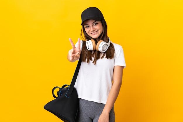 Młoda kobieta sport z torbą sportową na białym tle na żółtej ścianie, uśmiechając się i pokazując znak zwycięstwa