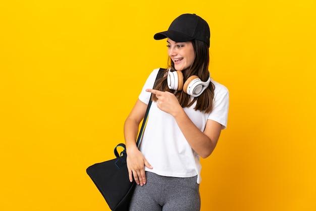 Młoda kobieta sport z torbą sportową na białym tle na żółtej ścianie, wskazując palcem na bok i prezentuje produkt