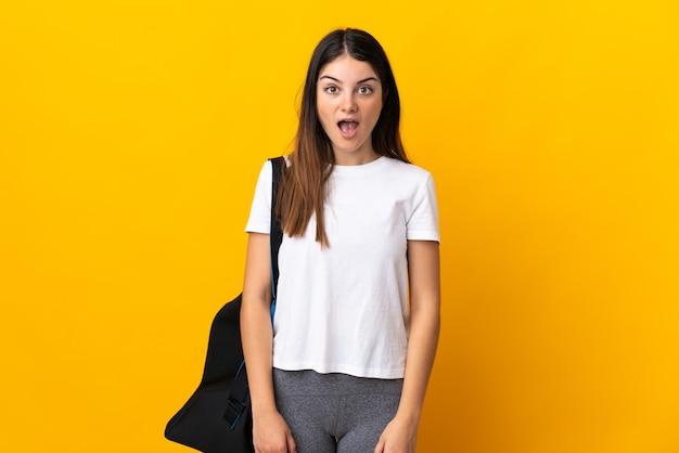 Młoda kobieta sport z torbą sportową na białym tle na żółtej ścianie z wyrazem twarzy zaskoczenia