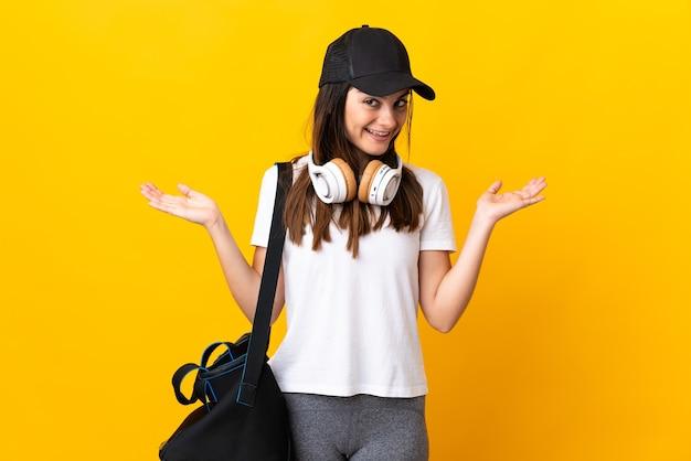 Młoda kobieta sport z torbą sportową na białym tle na żółtej ścianie z zszokowanym wyrazem twarzy