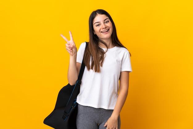 Młoda kobieta sport z torbą sportową na białym tle na żółty uśmiechnięty i pokazujący znak zwycięstwa