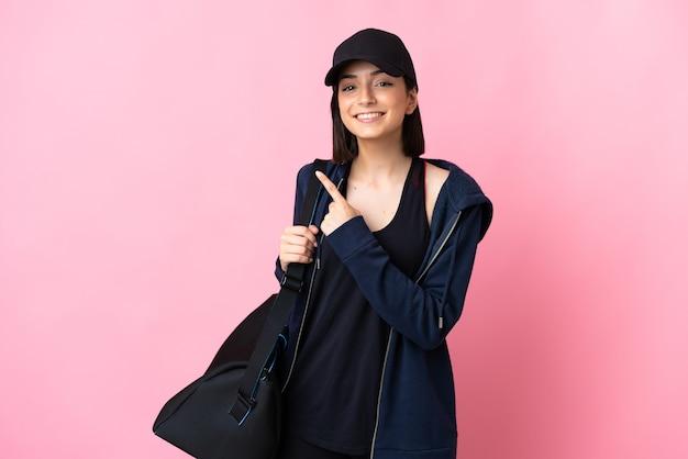 Młoda kobieta sport z torbą sportową na różowym tle, wskazując na bok, aby przedstawić produkt