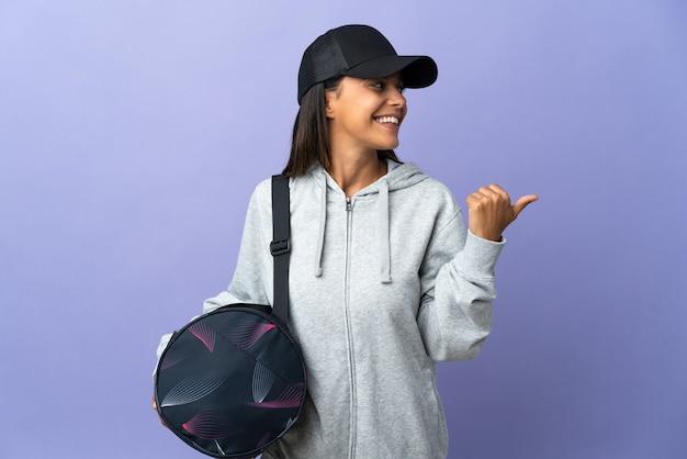 Młoda kobieta sport z torbą sportową skierowaną w bok, aby przedstawić produkt
