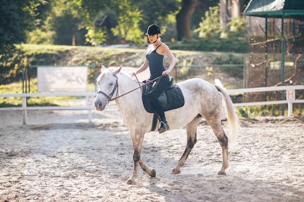 Młoda kobieta sportowa jedzie na koniu