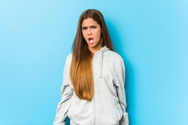 Młoda kobieta sportowa krzyczy bardzo zły i agresywny.