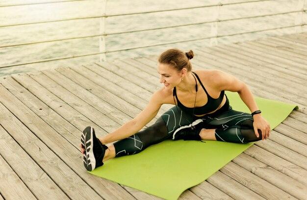 Młoda kobieta sportowa w odzieży sportowej rozciąga jedną nogę siedząc na macie na drewnianym tarasie na plaży
