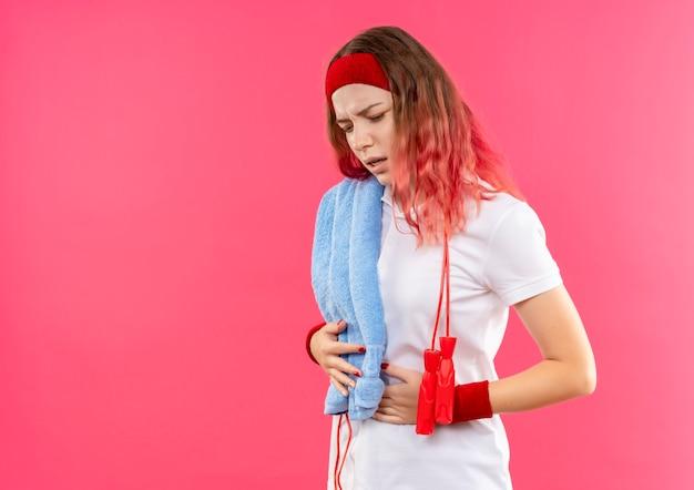 Młoda kobieta sportowa w opasce z ręcznikiem na ramieniu wyglądająca na zmęczoną i wyczerpaną, dotykając jej brzucha stojącego na różowej ścianie