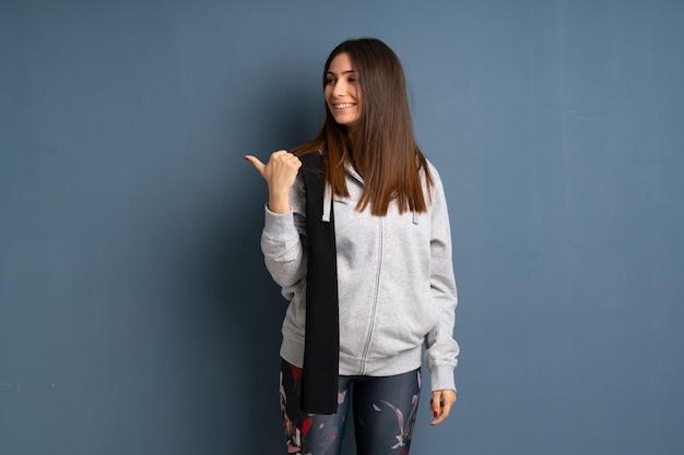 Młoda kobieta sportowa wskazująca na bok, aby przedstawić produkt