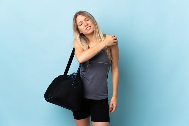 Młoda kobieta sportowa z torbą sportową na białym tle na niebieskiej ścianie cierpi na ból barku z powodu wysiłku