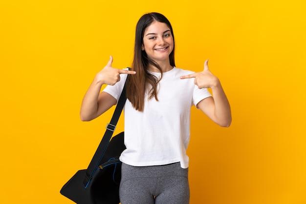 Młoda kobieta sportowa z torbą sportową na białym tle na żółtej ścianie dumna i zadowolona z siebie