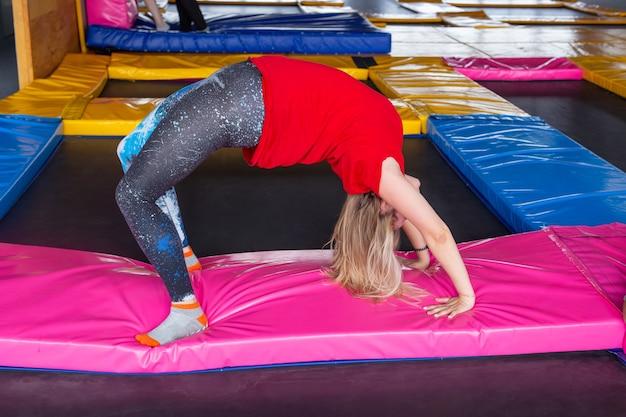 Młoda kobieta sportowca na trampolinie w fitness park i robienie ćwiczeń w pomieszczeniu.