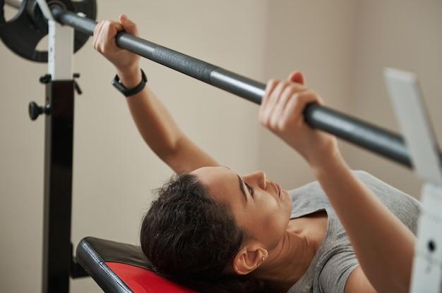 Młoda kobieta sportowiec skoncentrowana na wykonywaniu wyciskania na ławce. zbliżenie.