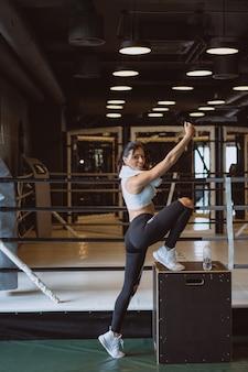 Młoda kobieta sportowy biorąc selfie z telefonu komórkowego dla sieci społecznościowych na siłowni.