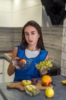 Młoda kobieta sportowy cięcia świeżych owoców różnych na drewnianym stole w kuchni. zdrowe jedzenie