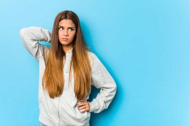 Młoda kobieta sportowy dotykając tyłu głowy, myślenia i dokonywania wyboru.
