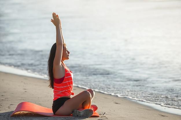 Młoda kobieta sportowy robi ćwiczenia jogi na plaży
