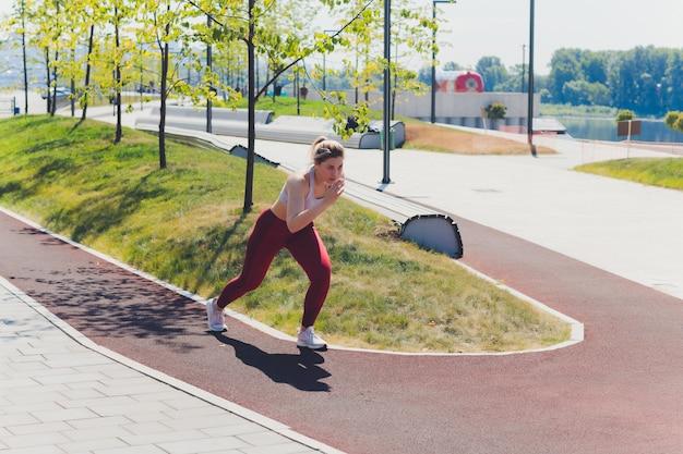 Młoda kobieta sportowy robi ćwiczenia rozciągające promenady.
