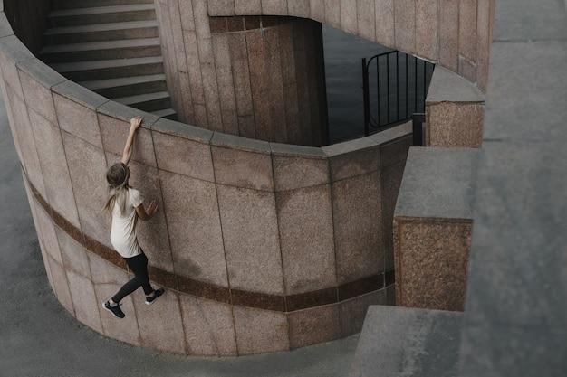 Młoda kobieta sportowy robi parkour w mieście. dziewczyna zaangażowana w freerunning.