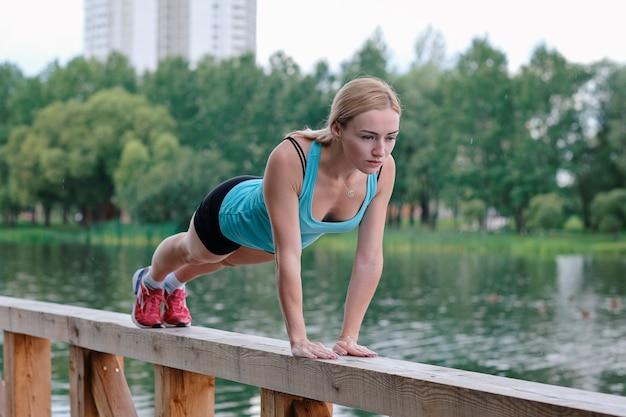 Młoda kobieta sportowy robi sport na świeżym powietrzu, ćwiczenia fitness.