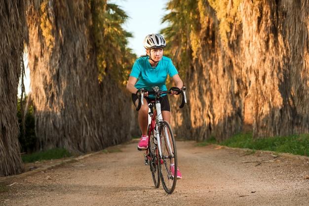 Młoda kobieta sportowy rowerzysta jazda rowerem na drodze z palmami w słoneczny dzień