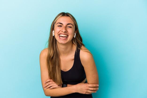 Młoda kobieta sportowy, słuchanie muzyki przez słuchawki na białym tle, śmiejąc się i dobrze się bawiąc