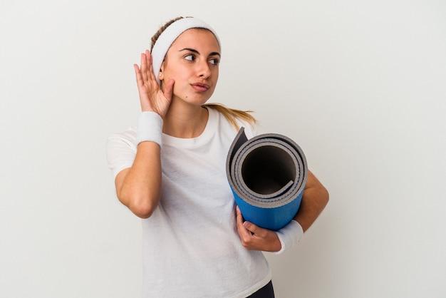 Młoda kobieta sportowy trzymając matę na białym tle próbuje słuchać plotek.