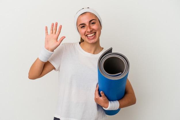 Młoda kobieta sportowy trzymając matę na białym tle uśmiechnięty wesoły pokazując numer pięć palcami.