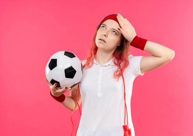 Młoda kobieta sportowy w opasce trzyma piłkę nożną patrząc zmęczony i wyczerpany stojąc na różowej ścianie