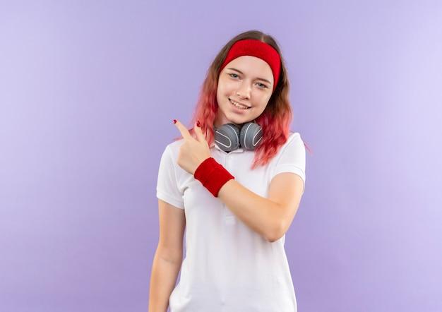 Młoda kobieta sportowy ze słuchawkami, uśmiechając się radośnie, wskazując wstecz stojącego na fioletowej ścianie