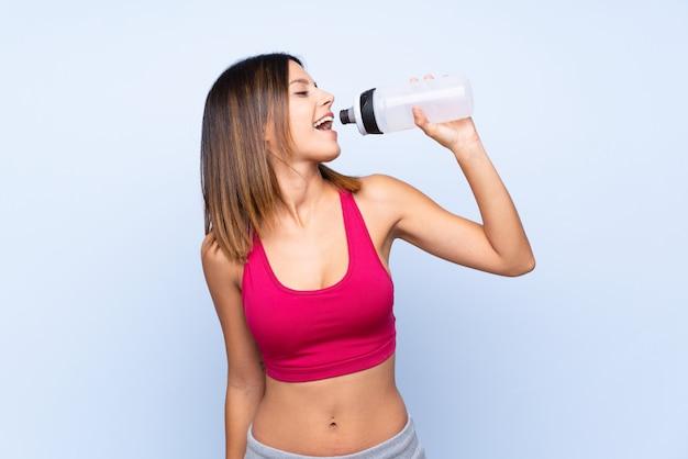 Młoda kobieta sportu na białym tle niebieski z butelek wody sportowe