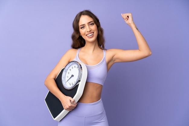 Młoda kobieta sportu na fioletowe ściany, trzymając maszynę ważącą i robi silny gest