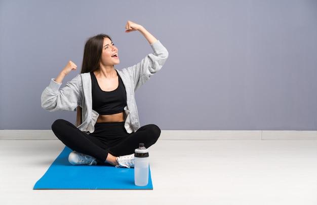 Młoda kobieta sportu siedzi na podłodze z matą świętuje zwycięstwo