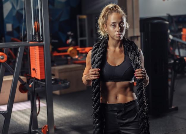 Młoda kobieta sportu w odzieży sportowej z liny bitwy na szyi w siłowni. trening funkcjonalny. pojęcie zdrowego stylu życia