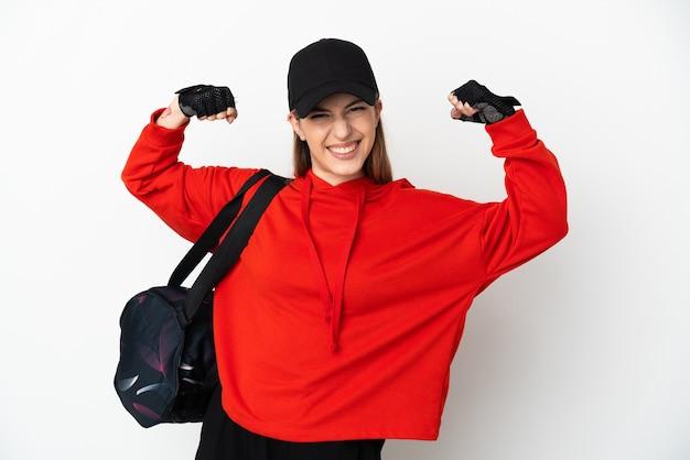 Młoda kobieta sportu z torbą sportową na białym tle