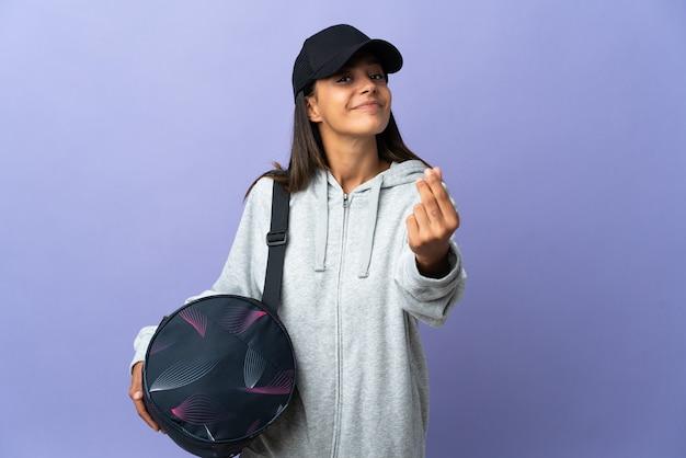 Młoda kobieta sportu z torbą sportową robi pieniądze gestowi