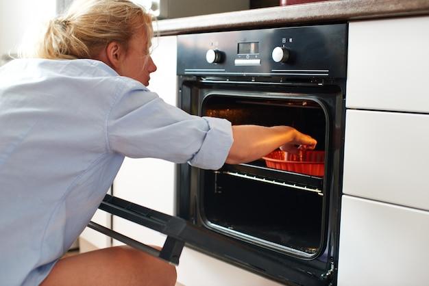 Młoda kobieta sprawdza deser w piekarniku