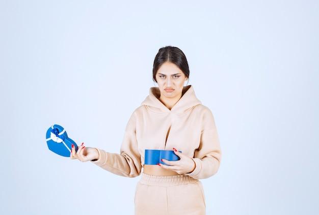 Młoda kobieta sprawdza niebieskie pudełko i wygląda na niezadowoloną