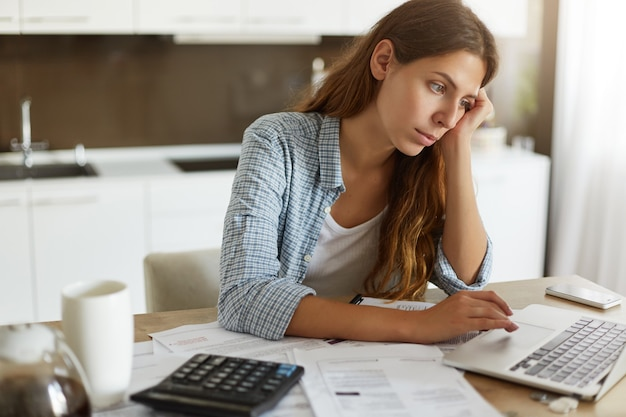 Młoda kobieta sprawdza swój budżet i robi podatki