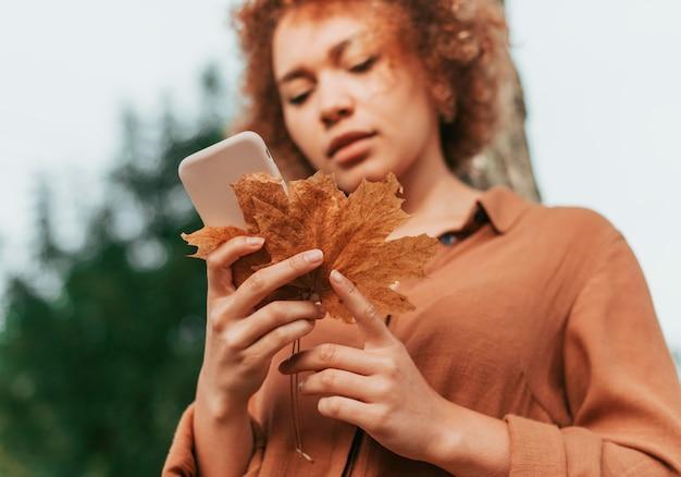 Młoda kobieta sprawdza swój telefon, trzymając suchy liść