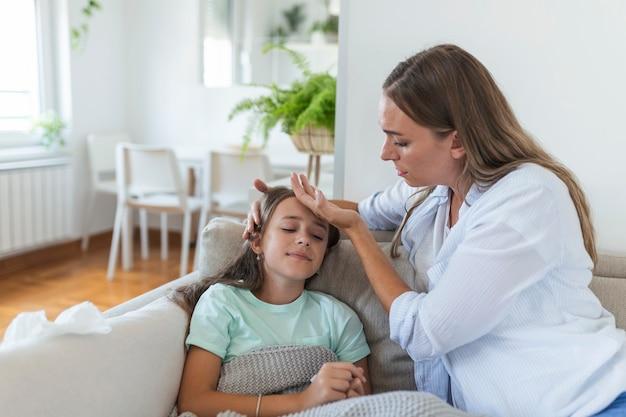 Młoda kobieta sprawdza temperaturę ręką małej chorej córki. matka sprawdza temperaturę swojej chorej dziewczynki. chore dziecko leżące na łóżku pod kocem z kobietą ręcznie sprawdzającą gorączkę na czole.