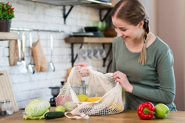 Młoda kobieta sprawdza torby z organicznie sklepami spożywczymi