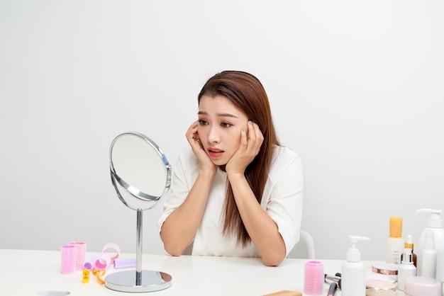 Młoda kobieta sprawdzająca jej skórę