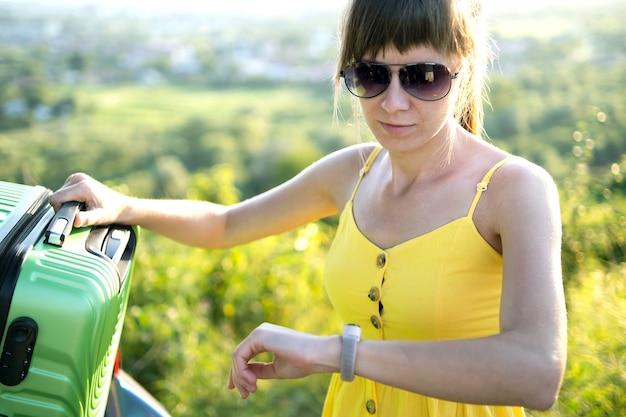 Młoda kobieta, sprawdzanie czasu podczas pakowania walizki w bagażniku samochodu