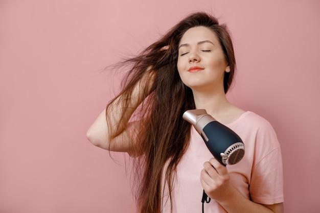 Młoda kobieta sprawia, że objętość włosów z suszarką w ręku na różowym tle