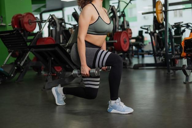Młoda kobieta sprawna rzuca się z hantlami. trening nóg na siłowni z wolnymi ciężarami. zdrowy tryb życia