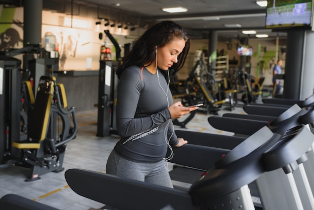 Młoda kobieta sprawny bieganie na bieżni, słuchanie muzyki przez słuchawki na siłowni. pojęcie zdrowego stylu życia.