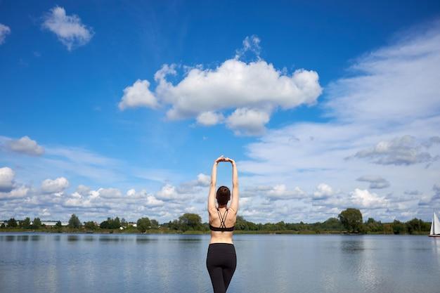 Młoda kobieta sprawny sobie czarną stylową odzież sportową rozciągający się w pobliżu jeziora na świeżym powietrzu.