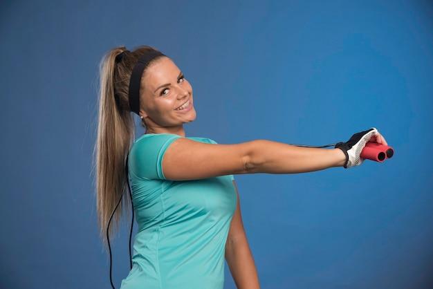 Młoda kobieta sprawny trzymając skakanki i rozciągając ramię.